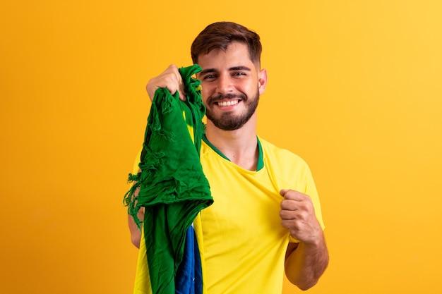 Brasilianischer fan jubelt in der menge auf gelbem hintergrund.