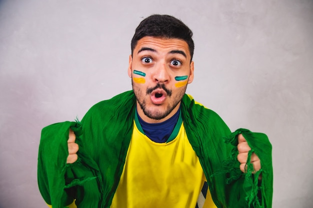 Brasilianischer fan mit einer flagge auf dem rücken jubelt brasilien zu, um zu gewinnen