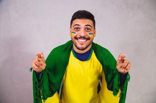 Brasilianischer fan mit einer flagge auf dem rücken jubelt mit gekreuzten daumen für den sieg brasiliens