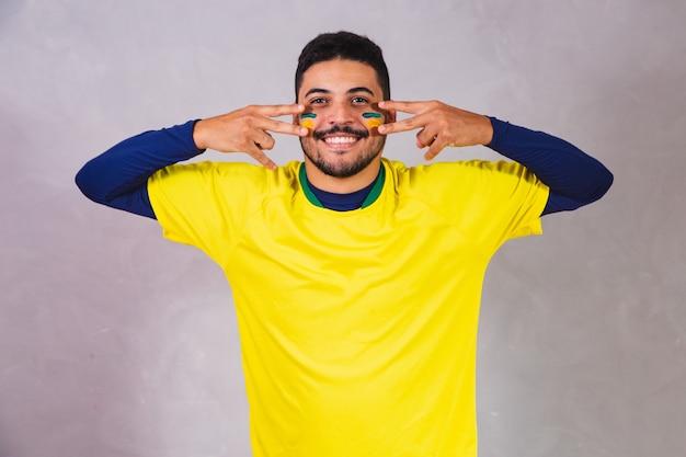 Brasilianischer fan. mit farbe als make-up, brasilianischer fan, der fußball- oder fußballspiel auf grauem hintergrund feiert. farben brasiliens.