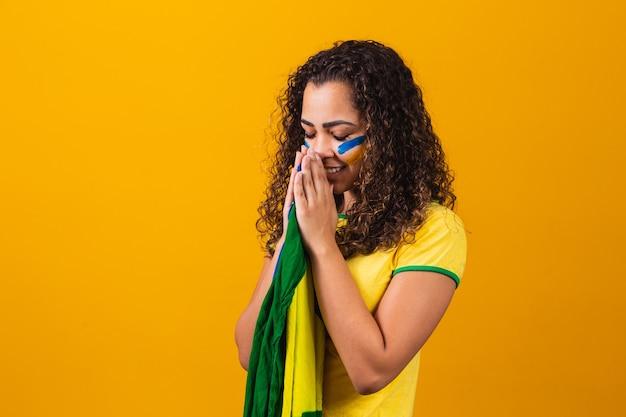 Brasilianischer fan mit flagge, die auf gelbem hintergrund betet. beten für brasilien