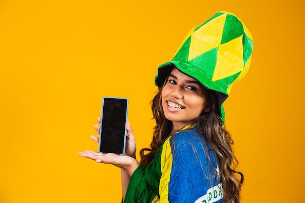 Brasilianischer fan. porträt, brasilianischer fan, der ihr handy zeigt, gekleidet als fußballfan oder fußballspiel auf gelbem hintergrund. farben brasiliens.wm