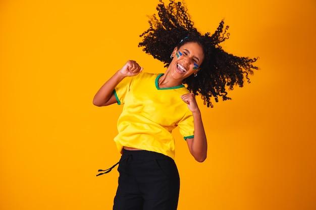 Brasilianischer fan. springen, um zu feiern, brasilianischer fan, der fußball- oder fußballspiel auf gelbem hintergrund feiert. farben brasiliens.
