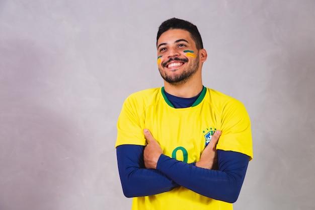 Brasilianischer fan trägt kostüm für die wm. brasilianischer männlicher fan in brasilianischer kleidung