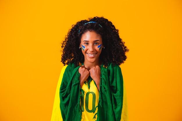 Brasilianischer fan. tragen der brasilianischen flagge in einem porträt, brasilianischer fan, der fußball oder fußballspiel auf gelbem hintergrund feiert. farben brasiliens.wm