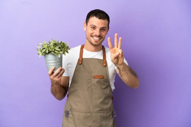 Brasilianischer gärtner, der eine pflanze über isoliertem lila hintergrund hält, glücklich und zählt drei mit den fingern