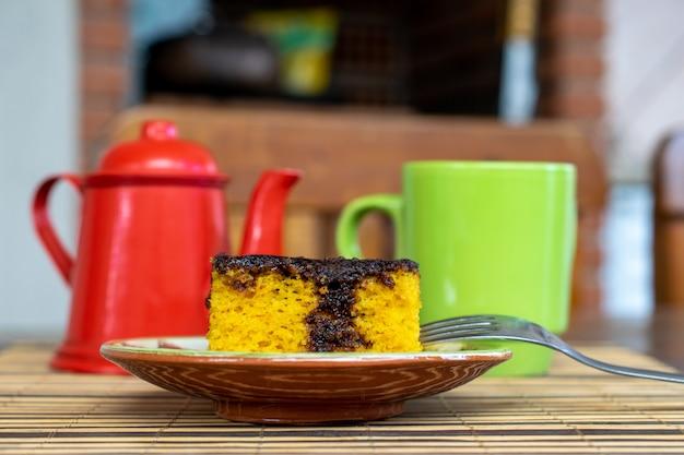 Brasilianischer karottenkuchen mit schokoladenglasur. teekanne und tasse im hintergrund defokussiert.