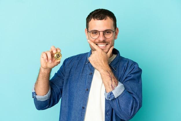 Brasilianischer mann, der einen bitcoin über isoliertem blauem hintergrund hält, glücklich und lächelnd