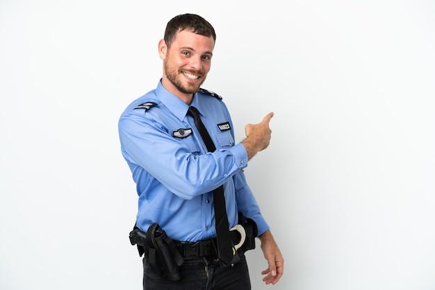 Brasilianischer mann der jungen polizei isoliert auf weißem hintergrund, der nach hinten zeigt