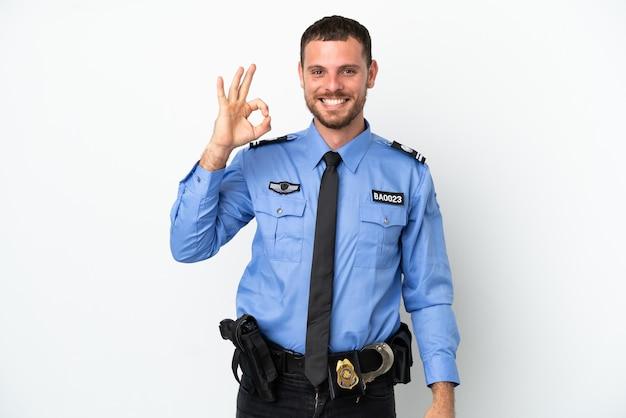 Brasilianischer mann der polizei isoliert auf weißem hintergrund, der mit den fingern ein ok-zeichen zeigt