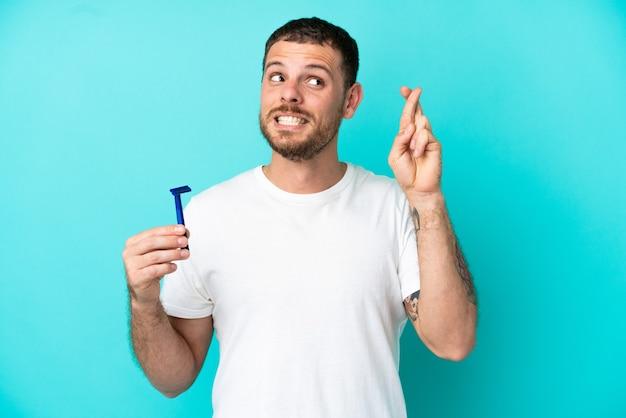 Brasilianischer mann, der seinen bart isoliert auf blauem hintergrund mit gekreuzten fingern rasiert und das beste wünscht