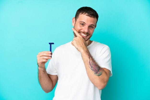 Brasilianischer mann, der seinen bart isoliert auf blauem hintergrund rasiert, glücklich und lächelnd