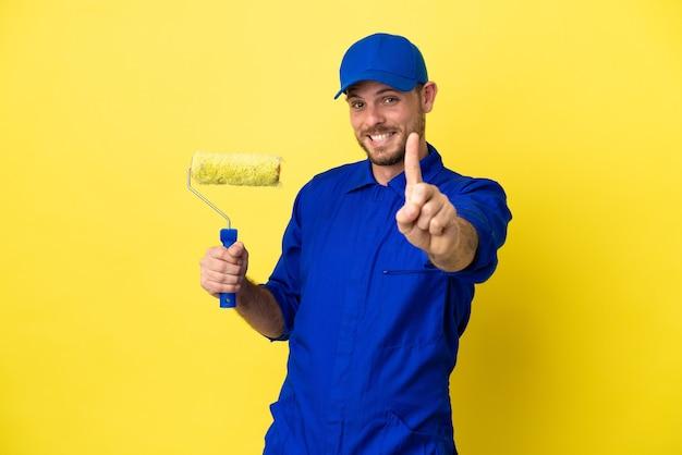Brasilianischer mann des malers lokalisiert auf gelbem hintergrund, der einen finger zeigt und anhebt