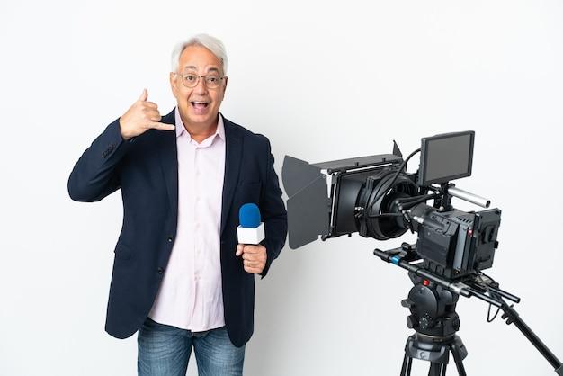 Brasilianischer mann des reporters mittleren alters, der ein mikrofon hält und nachrichten lokalisiert auf weißem hintergrund macht, der telefongeste macht. rufen sie mich zurück zeichen