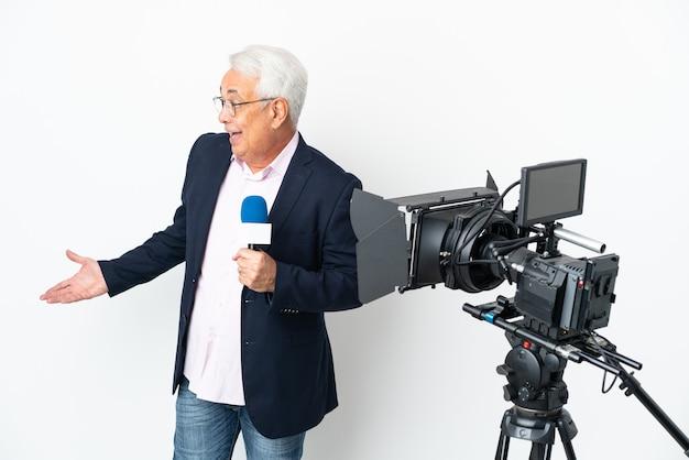 Brasilianischer mann des reporters mittleren alters, der ein mikrofon hält und nachrichten lokalisiert auf weißem hintergrund mit überraschungsausdruck beim betrachten der seite isoliert