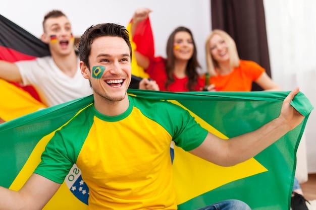 Brasilianischer mann mit freunden aus verschiedenen ländern, die den fußball im fernsehen genießen