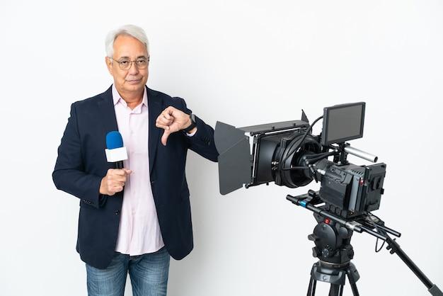 Brasilianischer mann mittleren alters des reporters, der ein mikrofon hält und nachrichten auf weißem hintergrund isoliert zeigt daumen unten mit negativem ausdruck zeigend