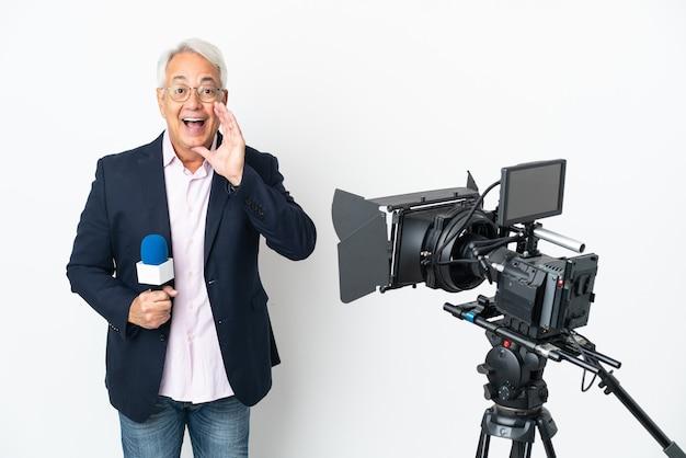 Brasilianischer mann mittleren alters des reporters, der ein mikrofon hält und nachrichten lokalisiert auf weißem hintergrund mit überraschung und schockiertem gesichtsausdruck berichtet