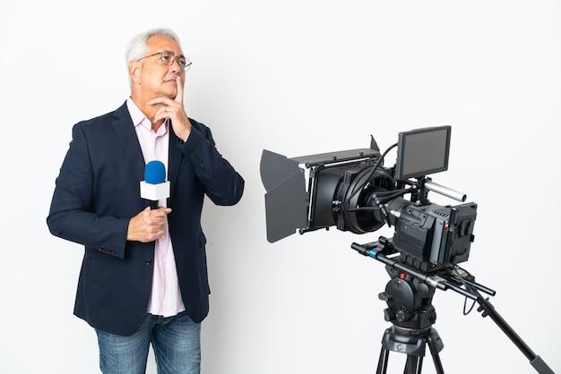Brasilianischer mann mittleren alters des reporters, der ein mikrofon hält und nachrichten lokalisiert auf weißem hintergrund mit zweifeln beim aufblicken berichtet