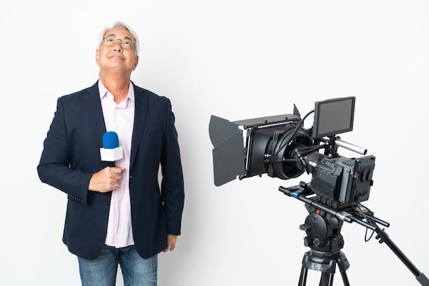 Brasilianischer mann mittleren alters des reporters, der ein mikrofon hält und nachrichten lokalisiert auf weißem hintergrund und nach oben schauend meldet