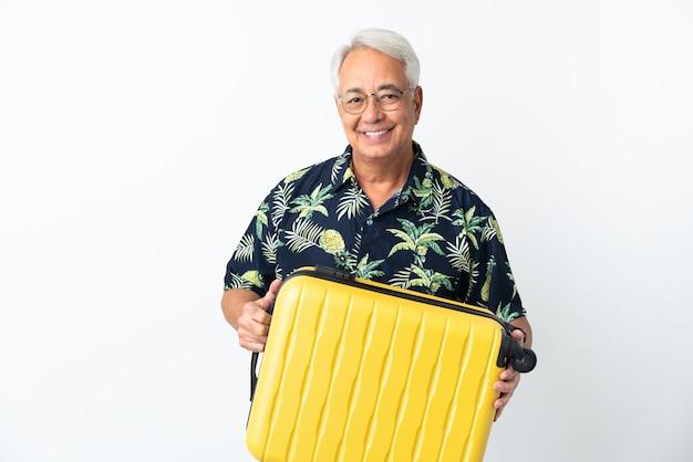Brasilianischer mann mittleren alters isoliert auf weißem hintergrund im urlaub mit reisekoffer