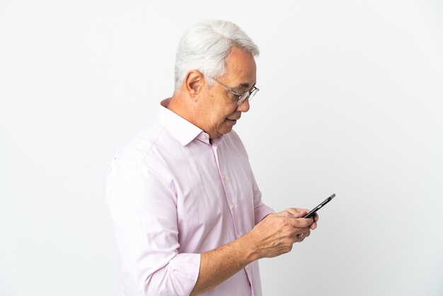 Brasilianischer mann mittleren alters isoliert das senden einer nachricht oder e-mail mit dem handy Premium Fotos