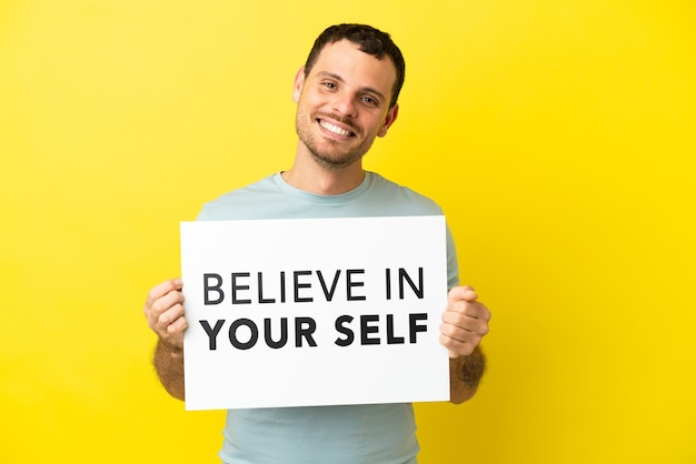 Brasilianischer mann über isoliertem lila hintergrund, der ein plakat mit dem text believe in your self mit glücklichem ausdruck hält