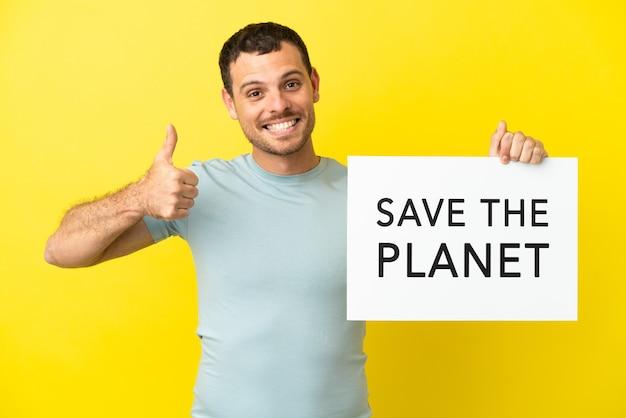 Brasilianischer mann über isoliertem lila hintergrund, der ein plakat mit dem text save the planet mit daumen nach oben hält