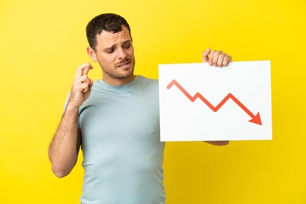 Brasilianischer mann über isoliertem lila hintergrund, der ein schild mit einem abnehmenden statistikpfeilsymbol mit gekreuzten fingern hält