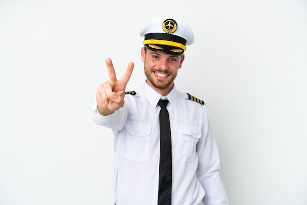Brasilianischer pilot des flugzeugs lokalisiert auf weißem hintergrund, der siegeszeichen lächelt und zeigt