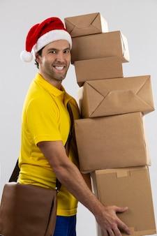 Brasilianischer postbote verkleidet als weihnachtsmann, der ein geschenk auf einem weißen hintergrund liefert. speicherplatz kopieren.