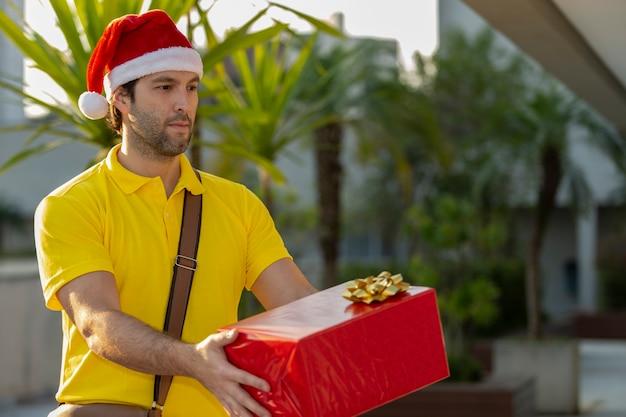 Brasilianischer postbote verkleidet als weihnachtsmann, der ein geschenk liefert.