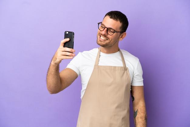 Brasilianischer restaurantkellner über isoliertem lila hintergrund, der ein selfie macht