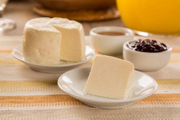 Brasilianischer schafskäse. brot, obst und verschiedene käsesorten im hintergrund.