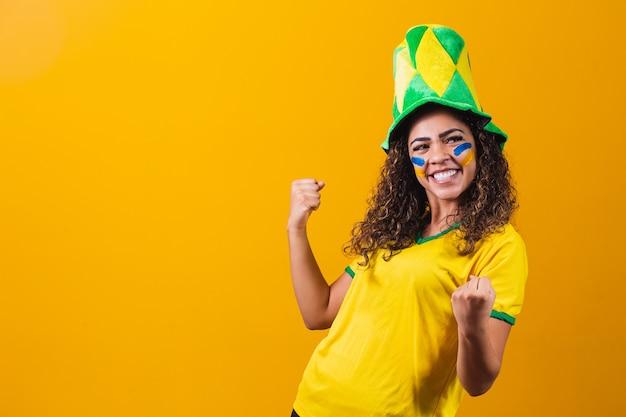 Brasilianischer unterstützer. brasilianischer frauenfan, der auf fußball- oder fußballspiel auf gelbem hintergrund feiert. brasilien farben. jawohl!