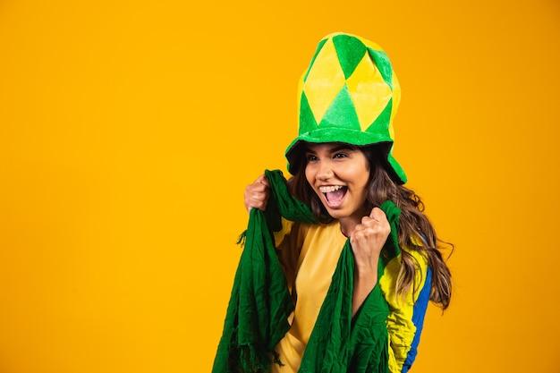 Brasilianischer unterstützer. brasilianischer frauenfan, der auf fußball- oder fußballspiel auf gelbem hintergrund feiert. brasilien farben.