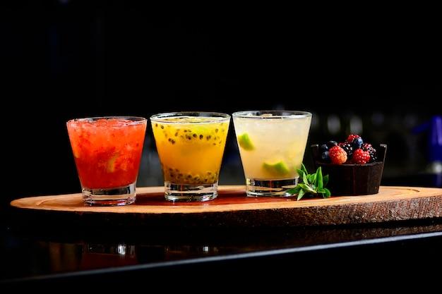 Brasilianisches caipirinha, zitronengetränk, passionsfruchtgetränk mit früchten und kräutern auf einem dunklen riegel