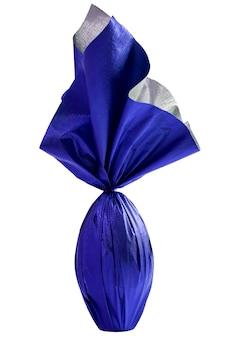 Brasilianisches easters-ei, eingewickelt in blaues papier auf einer weißen wand