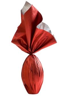 Brasilianisches easters-ei, eingewickelt in rotes papier auf einer weißen wand
