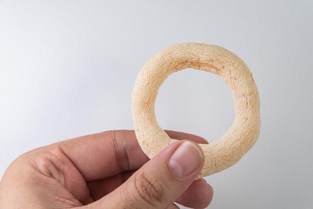 Brasilianisches essen - biscoito de polvilho - mann hält