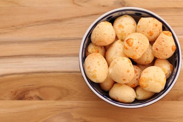 Brasilianisches essen und getränk - traditionelle käsebrotschüssel (pã £ o de queijo) auf einem holztisch