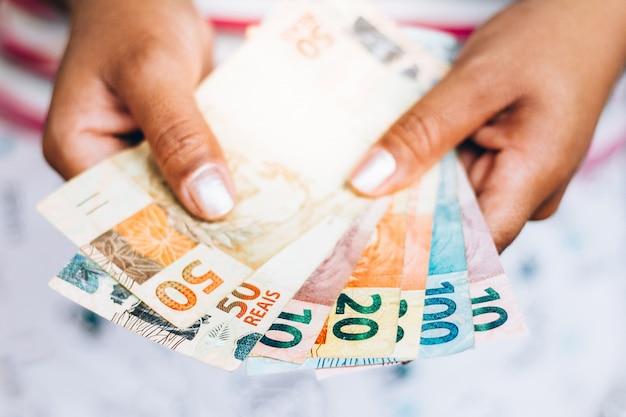 Brasilianisches geld - real notes - brasilianische währung - finanzkonzept - investitionen - reichtum - frau, die geld hält.