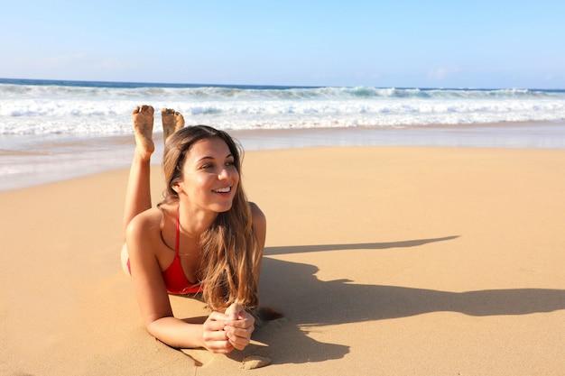 Brasilianisches lächelndes schönes mädchen, das sich auf sand legt und das sonnenbaden der sonne im badeanzug genießt