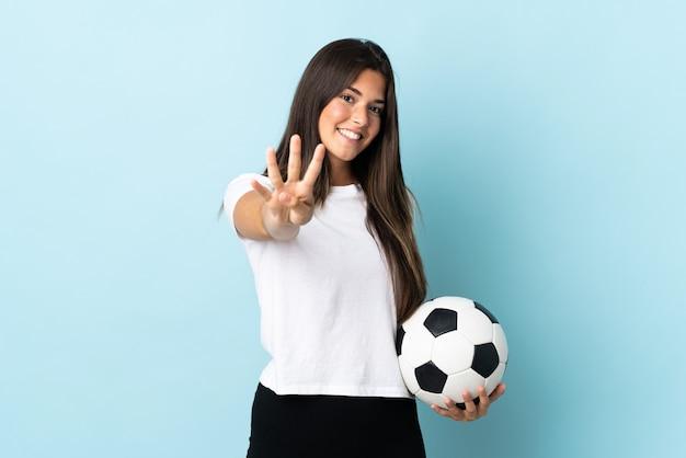 Brasilianisches mädchen des jungen fußballspielers lokalisiert auf blauem hintergrund glücklich und zählt vier mit den fingern