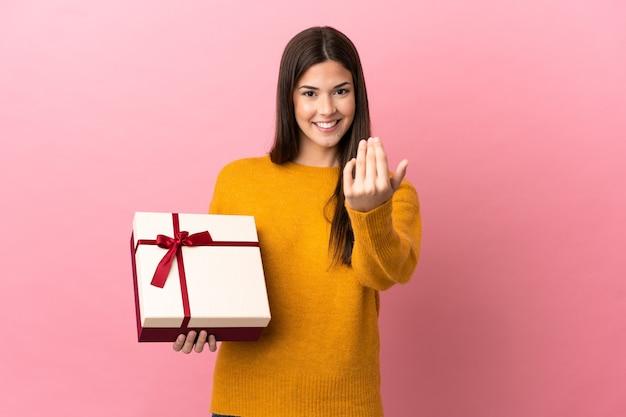 Brasilianisches mädchen des teenagers, das ein geschenk über lokalisiertem rosa hintergrund hält, das einlädt, mit der hand zu kommen. schön, dass du gekommen bist