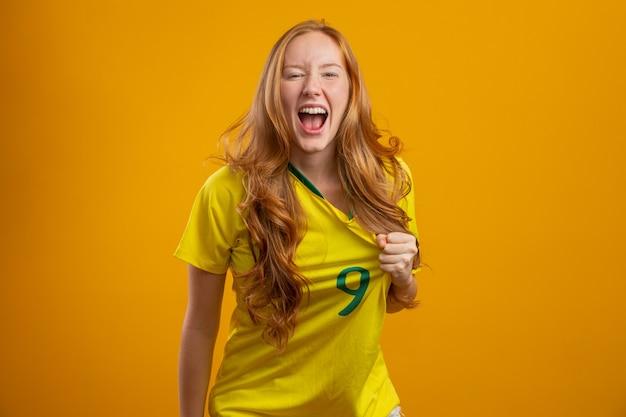 Brasilien anhänger. brasilianischer rothaariger frauenfan, der auf fußball-, fußballspiel-brasilienfarben feiert.