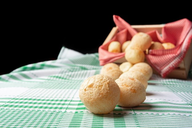 Brasilien käsebrot, käsebrötchen, die aus einer schachtel auf eine grün karierte tischdecke fallen, selektiver fokus.
