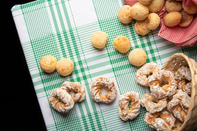 Brasilien-käsebrot und süßer keks auf einem tisch mit grün karierter tischdecke, draufsicht.