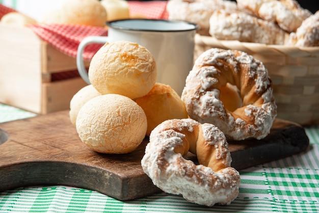 Brasilien käsebrot und süßer keks und eine tasse kaffee auf einem tisch mit grün karierter tischdecke, selektiver fokus.
