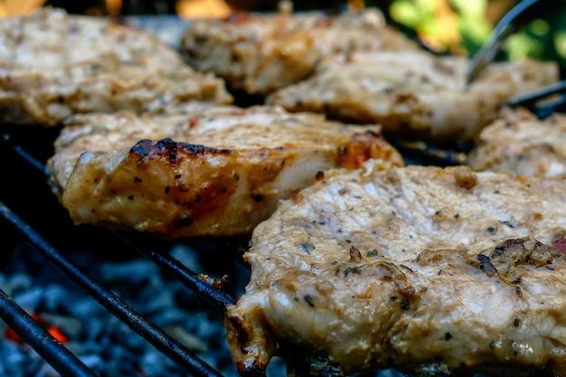 Braten saftige stücke von frischem schweinenackensteakfleisch, das auf grill oder grillgitter im freien im hinterhof zubereitet wird. auf holzkohle rauchen. nahaufnahme. draußen.